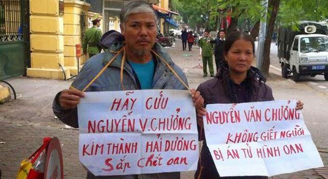Bố mẹ tử tù Nguyễn Văn Chưởng đeo biển kêu oan cho con. Ảnh: Trần Thị Nga