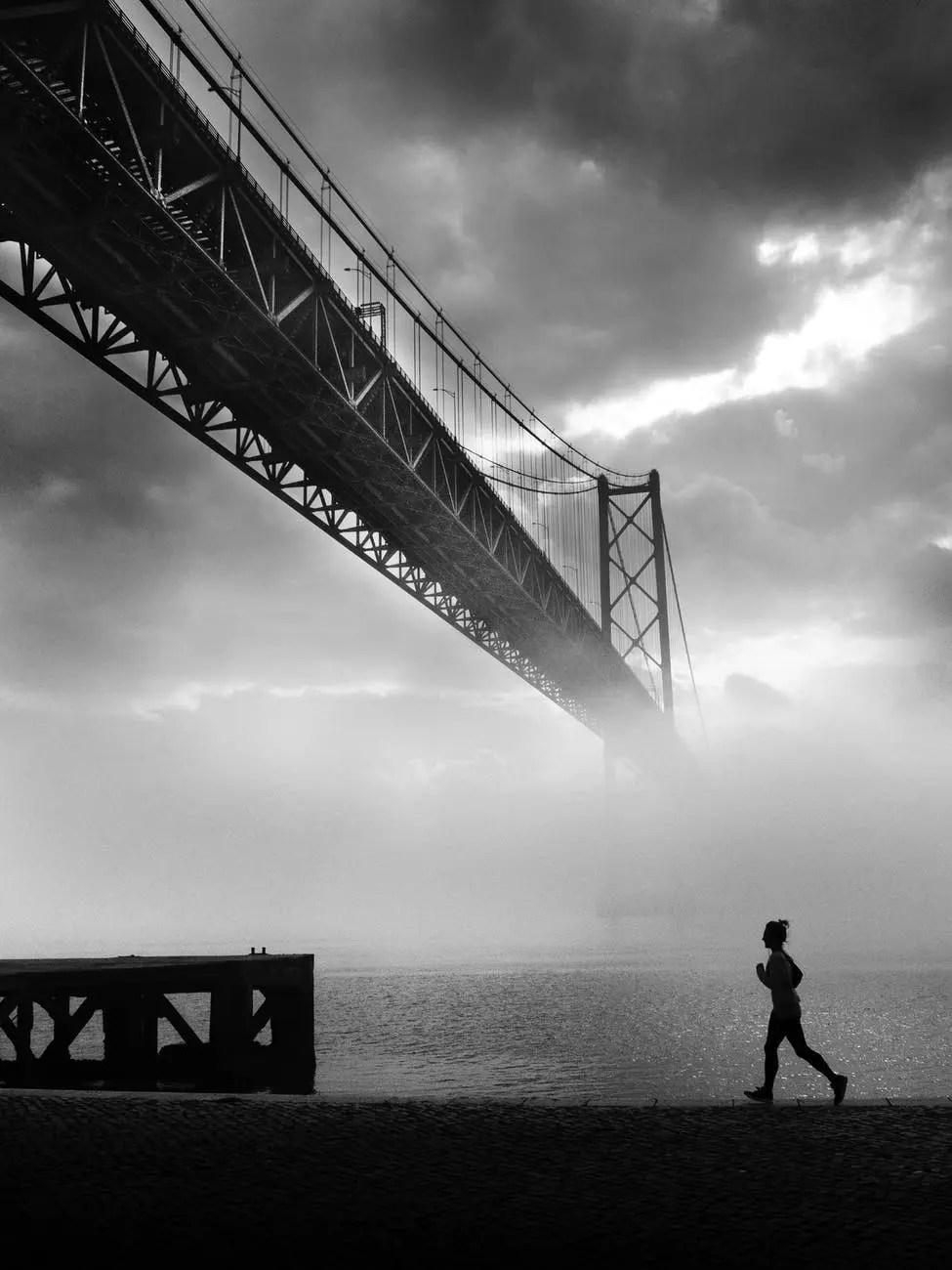 grayscale photo of person jogging near river