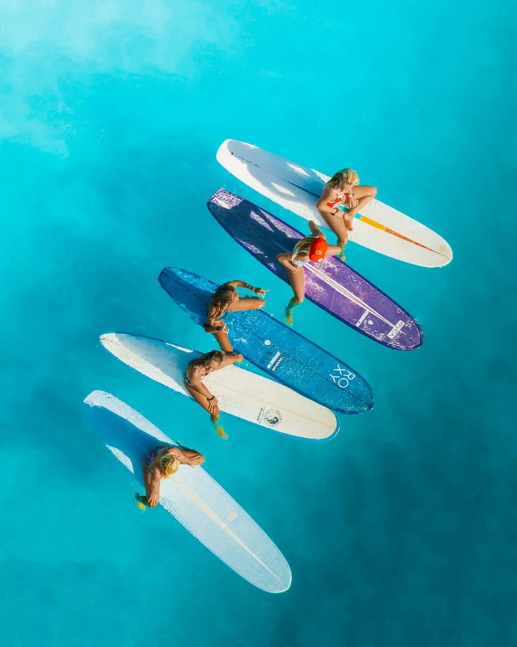 people riding on white and blue surfboard
