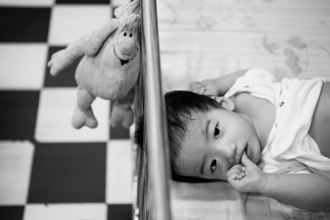 A young girl in her crib. A small plush toy hangs on the bars. An unknown future awaits this patient of the GoVap Orphanage. Ho Chi Minh City. Vietnam. 2007