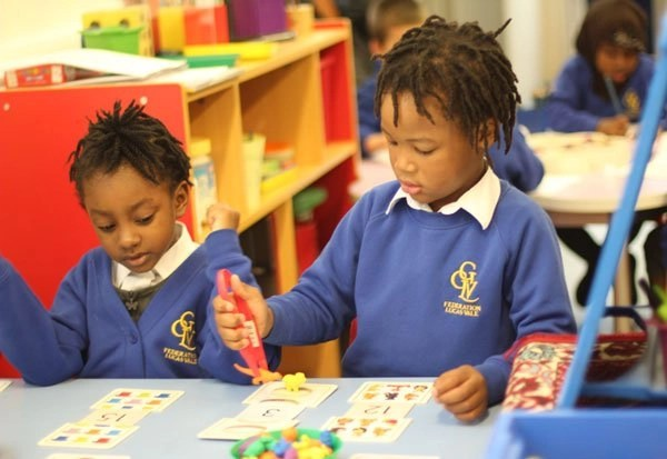 Two young children learning a Maths game
