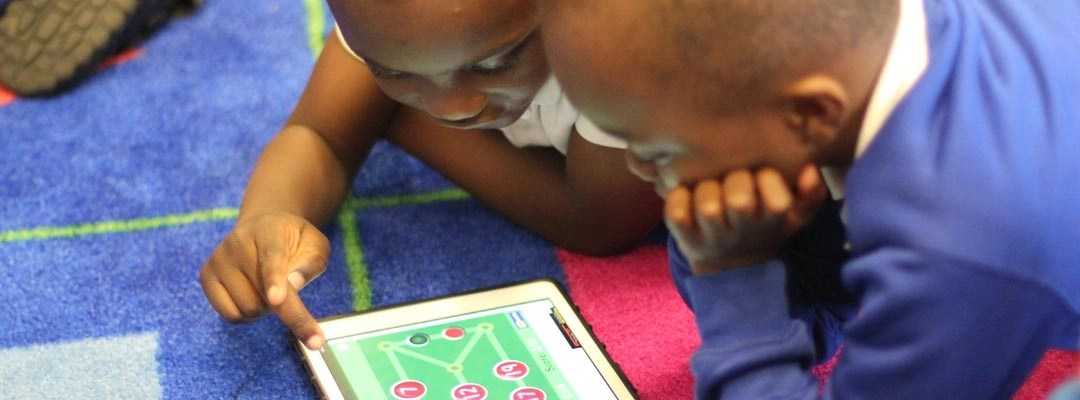 Children engrossed in using an iPad