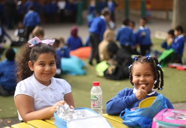 Children sitting in the school picnic area eating their packed lunch