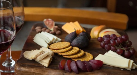 Cheese, crackers, grapes set up on a cutting board