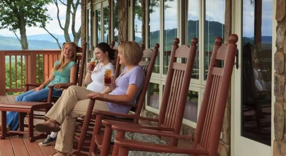 Three women sitting on the porch in brown rocking chairs.