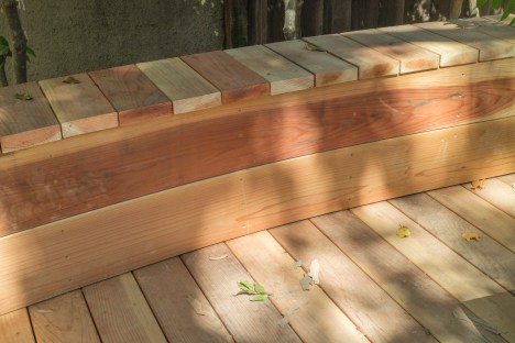 The seat wall has curved - or bent - facing. The top boards align with the decking.