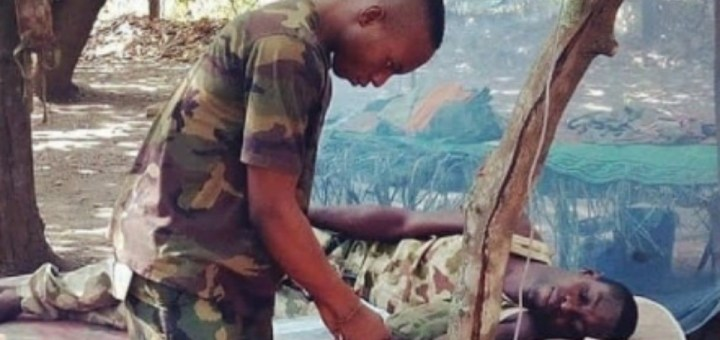 Viral Photo of a sick Nigerian Soldier receiving treatment on mattress supported by branches while his IV fluid hangs from a Tree