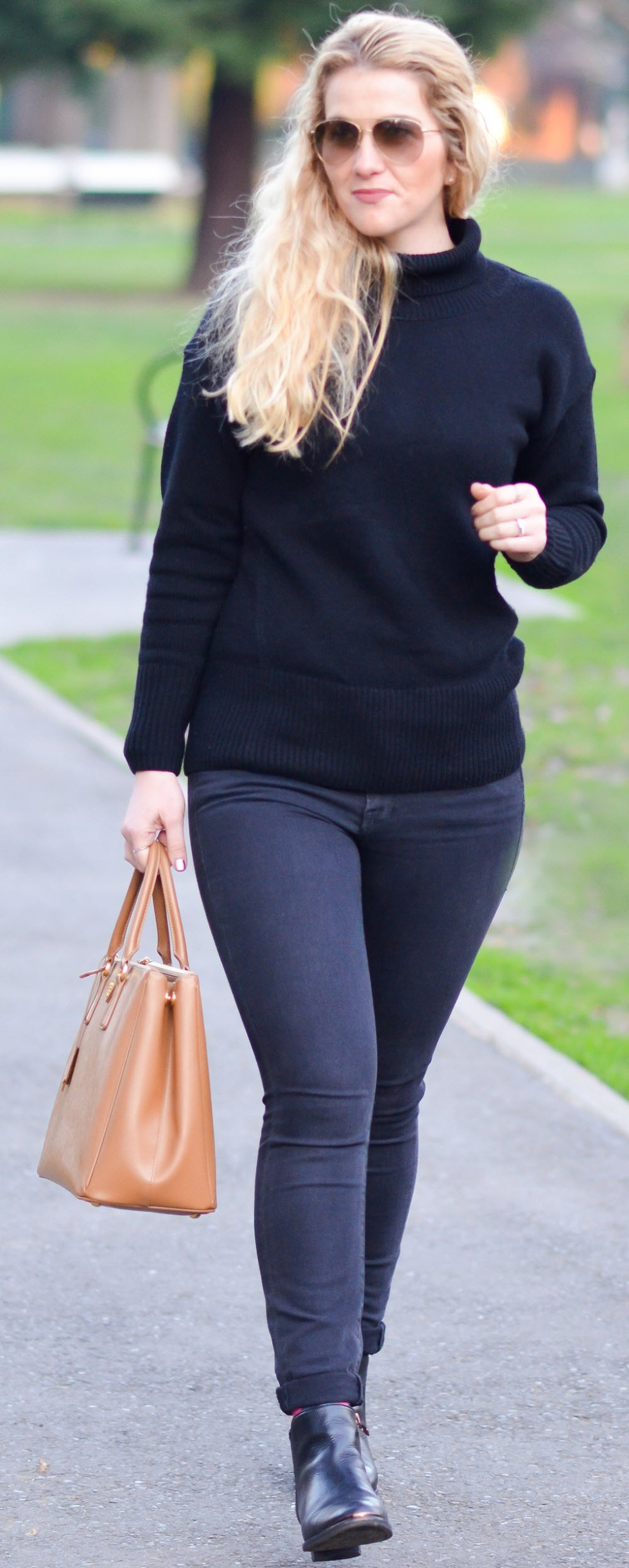 All black street style outfit w. Prada Saffiano Tote. Ankle Boots + Skinny Jeans Cuffed.