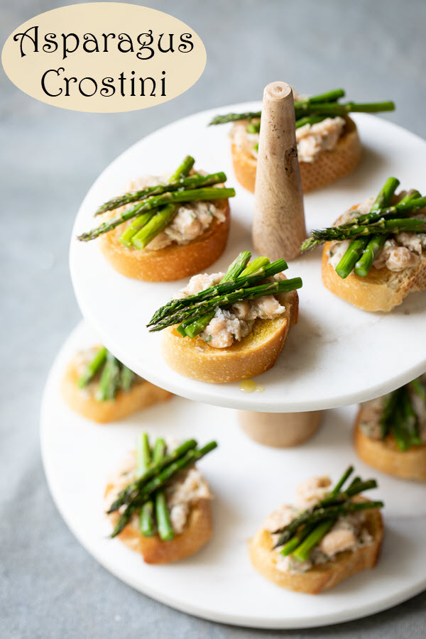 Cold Asparagus Appetizer - Asparagus Crostini. This appetizer is made with a white bean spread and topped with delicious fresh asparagus. A wonderful spring appetizer. This plant based recipe has protein, color, and vegetables! #lmrecipes #appetizers #entertaining #plantbased #vegan #asparagus