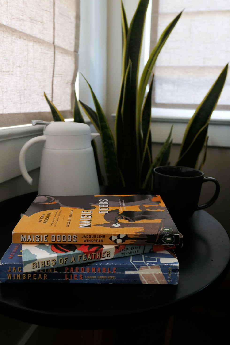 First 3 books of Maisie Dobbs Series Stacked on Side Table