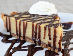 Butterscotch Pudding Pie with chocolate graham cracker crust, fresh whipped cream and chocolate sauce
