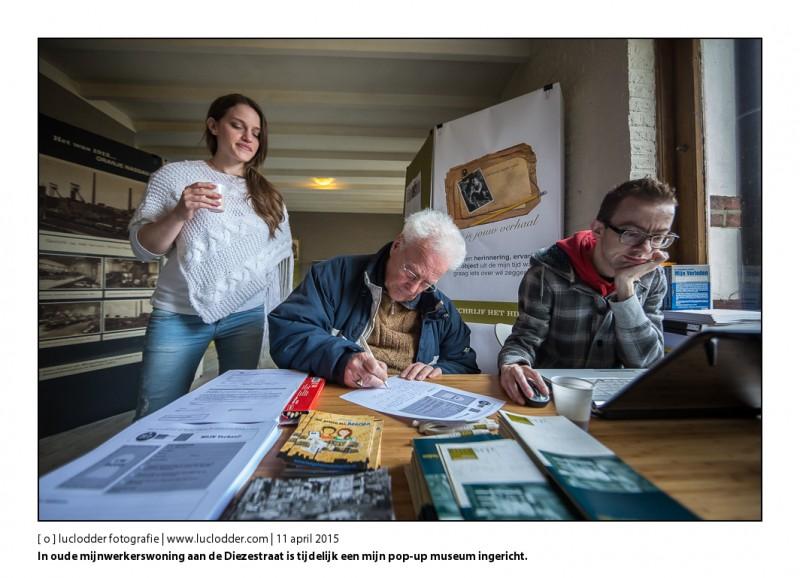 Dhr. R. Minartz (oud mijnwerker) schrijft zijn verhaal op het blaadje voor aan de prikwand. In oude mijnwerkerswoning aan de Diezestraat is tijdelijk een mijn pop-up museum ingericht. Georganiseerd door Kate Heuts (Links) als afstudeerproject. Rechts in beeld de ons ontvallen Maurice van Opdorp mede initiatief nemer van Heerlen Vertelt.