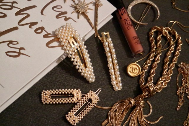 A selection of pearl hair clips, a Chanel necklace and tassel bracelet draped across a grey back ground and book
