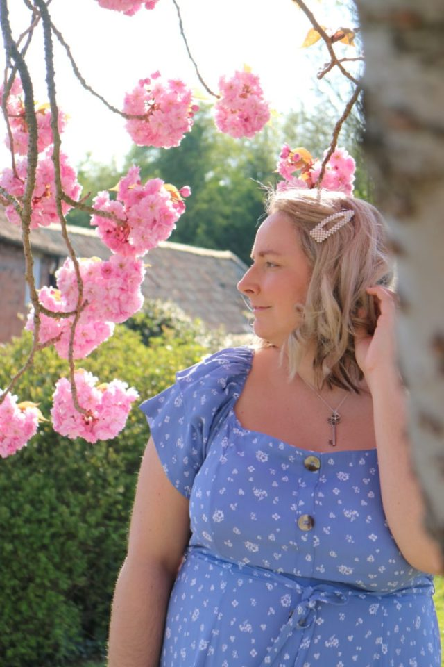 lucy in a blue river island dress stood with a blossom tree