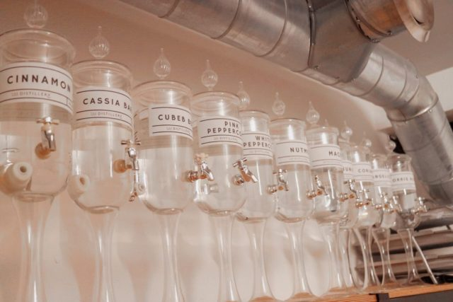 glass jars with clear flavoured liquids in to add to gin