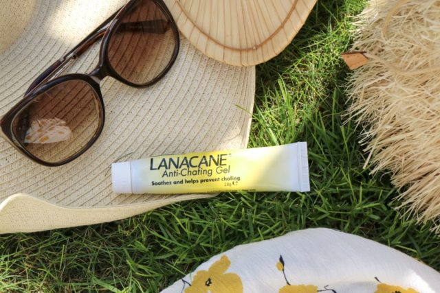 lanacane anti chafing gel on grass with a straw hat and sunglasses