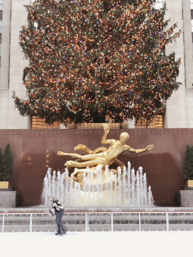 ice skating in front of the Rockefeller Tree and golden statue and fountain in New York