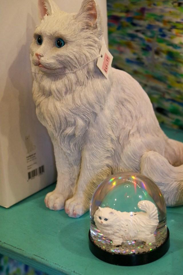 a cat money box and glitter globe