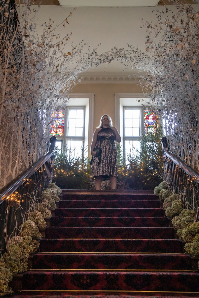 lucy in the sequin dress stood at the top os some stairs with stained glass behind and trees and hydrangea's lining the stairs