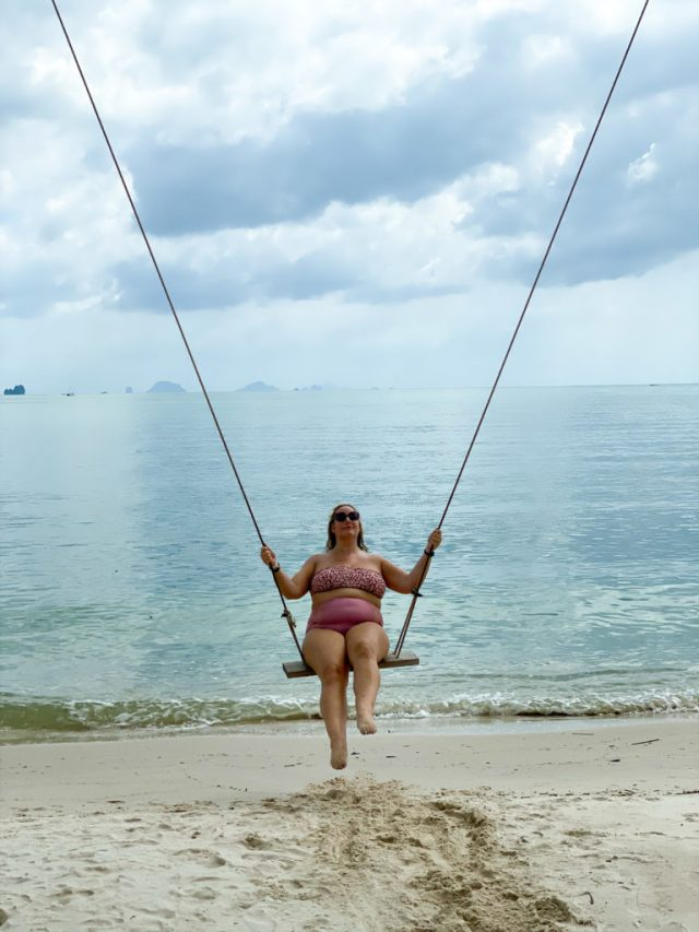lucy on a swing with the sea behind her