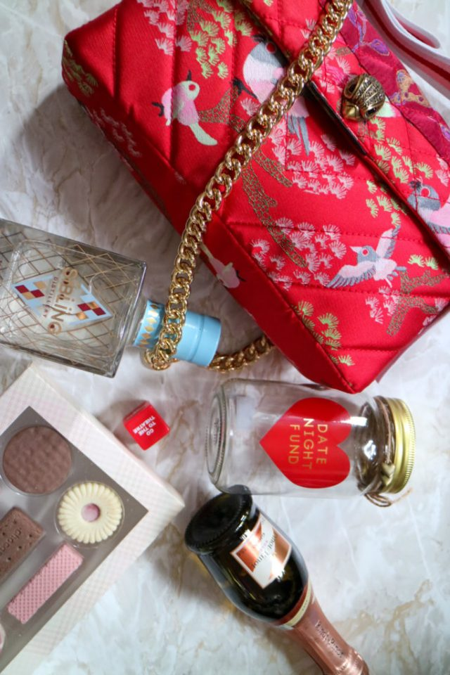 kurt geiger red bag with gin, date nigt jar and chocolates around it