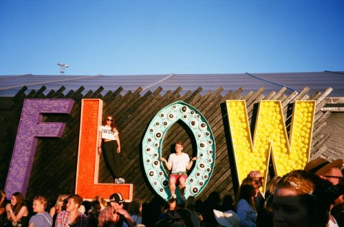 People in front of large letters spelling FLOW