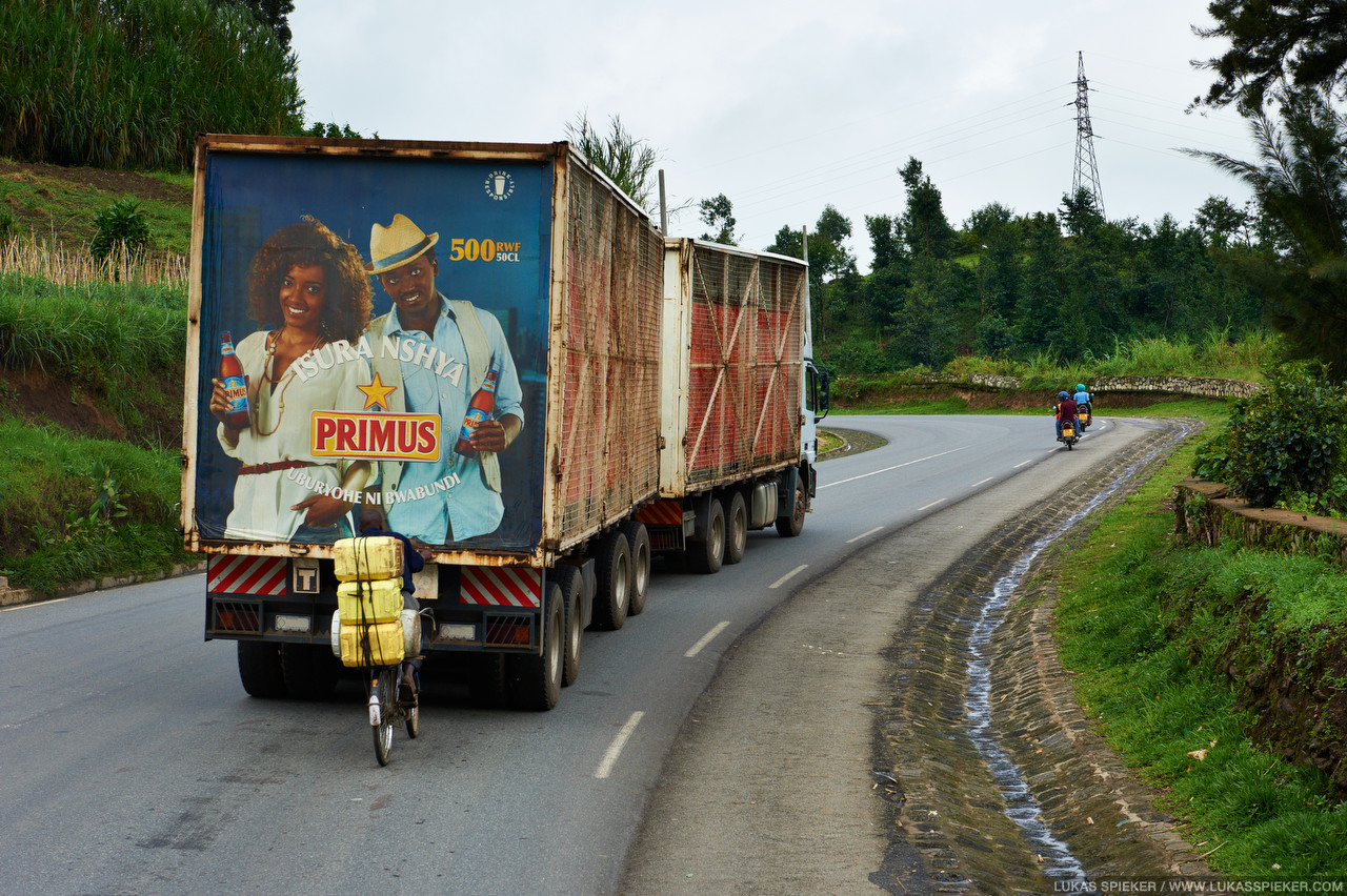 A cyclist gets a grip on a truck to let it pull him uphill. In Rwanda, the land of a thousand hills, cargo bicycles are widely used for the transportation of goods and passengers.