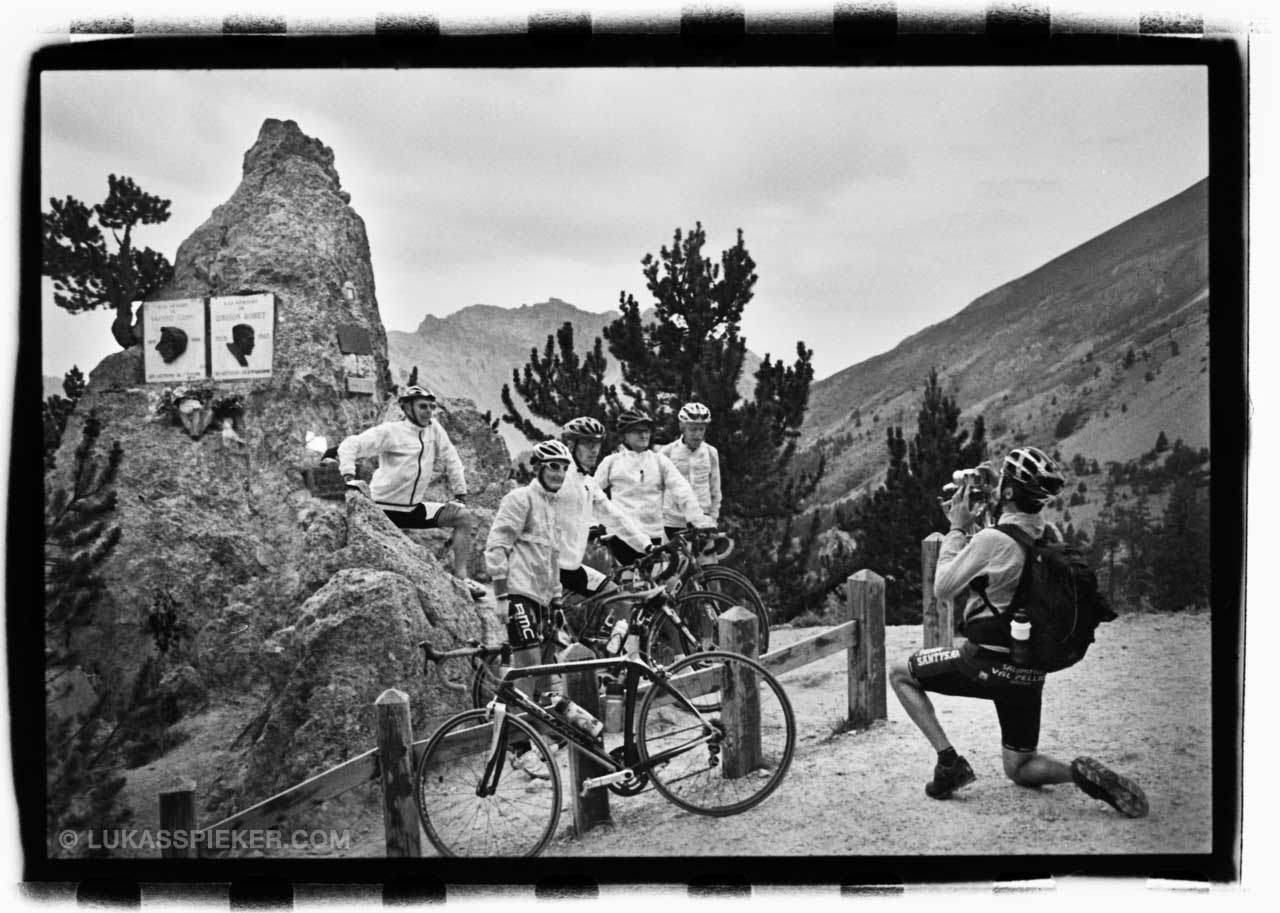 Italian cyclists take a photo in front of the Fausto Coppi memorial monument at the Col d'Izoard in the morning before the Tour de France passes, July 19, 2014.