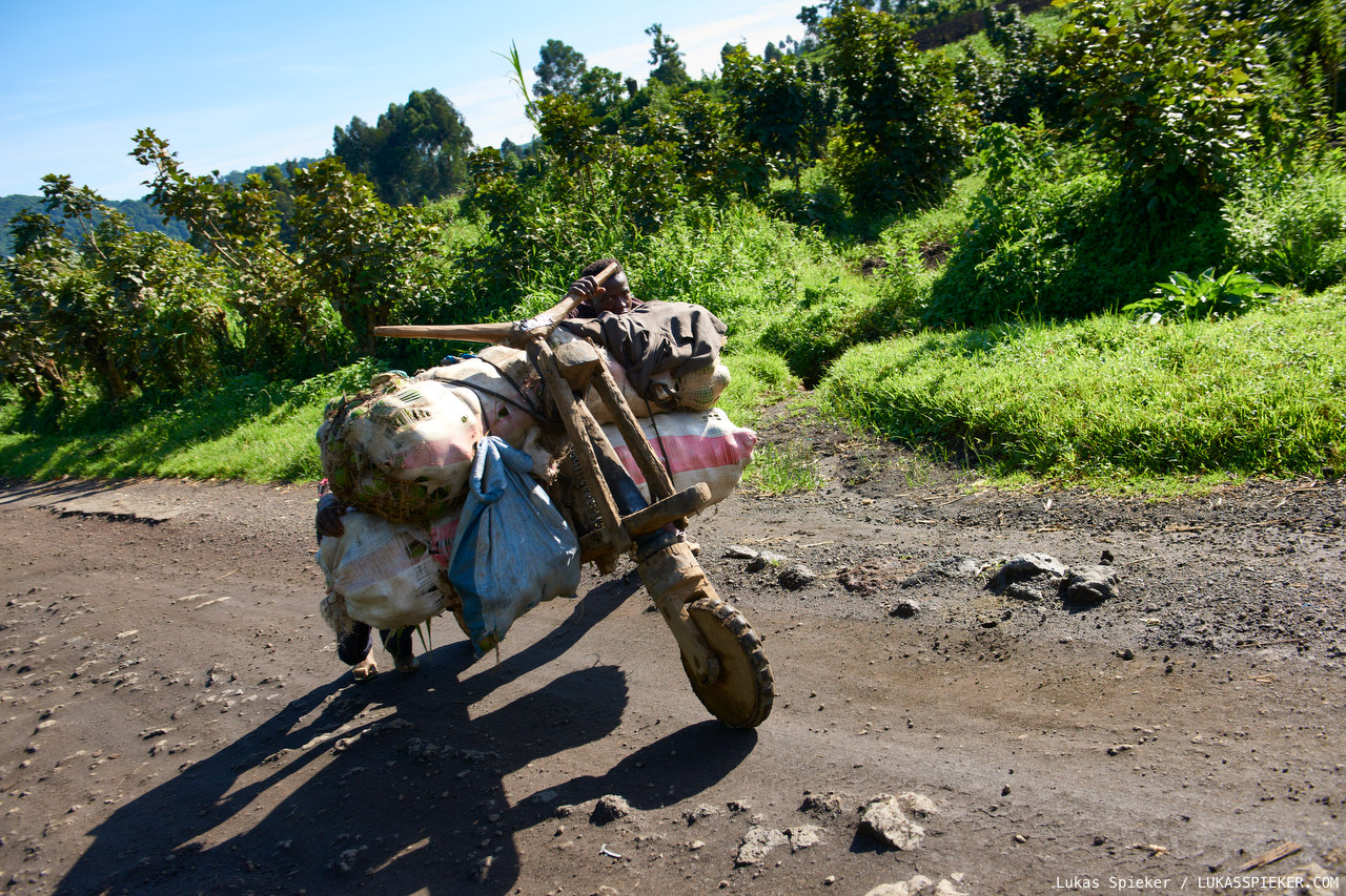 Two men push a heavily loaded Chukudu uphill on the road from Goma to the North in the Democratic Republic of the Congo. Chukudu transport bicycles are built from wood and spare parts of old disused cars. They are used for the transportation of loads of several hundred kilograms.