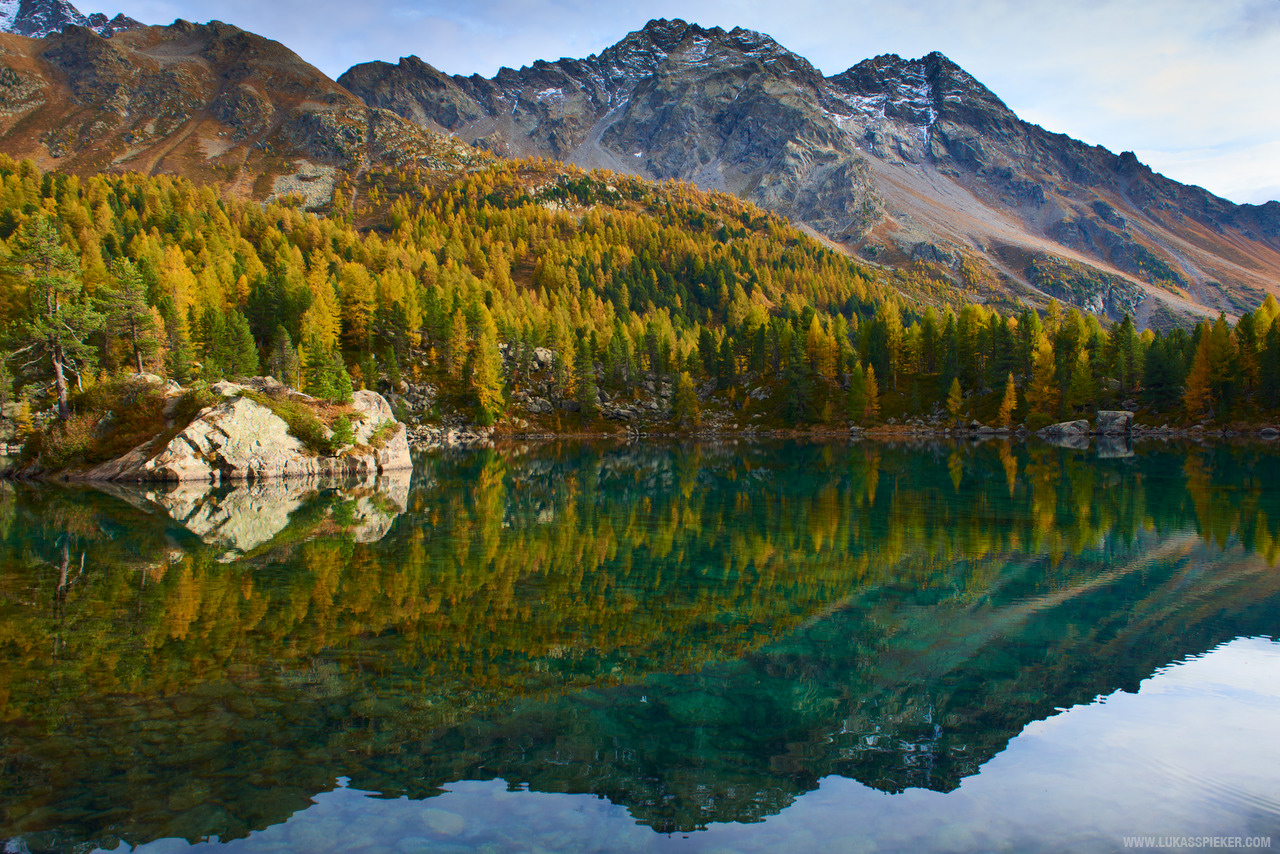 The colours of the autumn forest reflect in a lake in a small valley in Switzerland's Val Poschiavo.