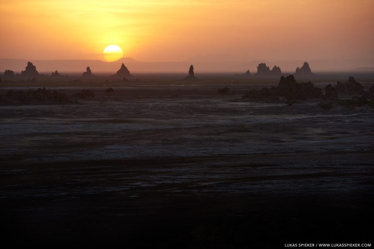 The sun sets behind limestone chimneys with steaming hot springs near Lac Abbe at the border between Djibouti and Ethiopia. Lac Abbe is a hypersalinic salt lake in the centre of the Afar Depression in the North of the East African Rift. The area is inhabited by Afar people herding camels, sheep, and goats.