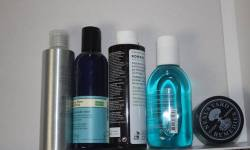 a picture of four different shampoo bottles, and a small glass tub.