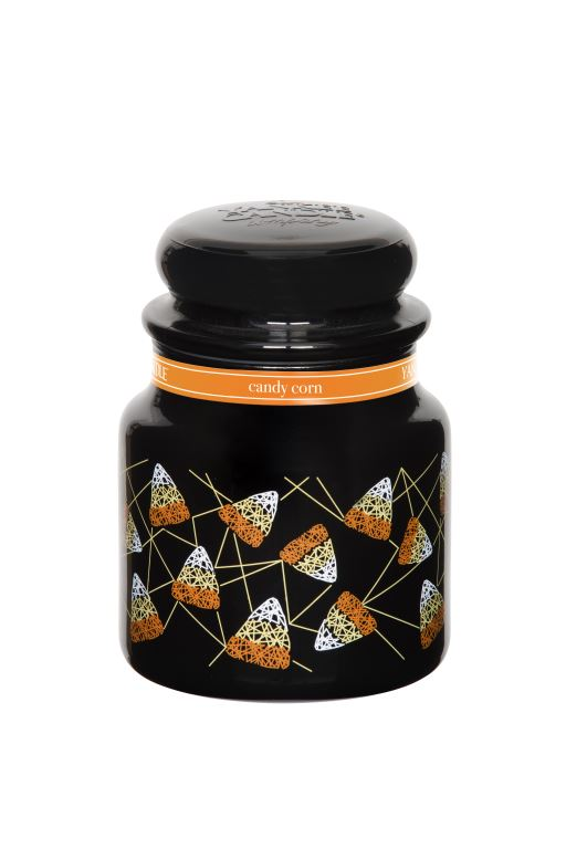 A black candle, with an orange label, and pictures of Candy Corn on it, on a white background.