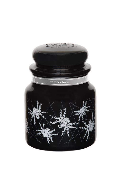 A black candle, with a grey label with pictures of Spiders on the label, on a white background.