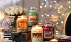 A collection of four tall glass jar candles that include Yankee Candle All Is Bright, Yankee Candle Star Anise & Orange, Yankee Candle festive Cocktail, and Yankee Candle Macaron Treats, on a wooden table, with some fairy lights in the background.