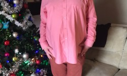Me wearing a Light pink shirt, some burgundy Chinos, and some pale pink boots with white laces, with a green Christmas tree and twinkly blue lights in the background.
