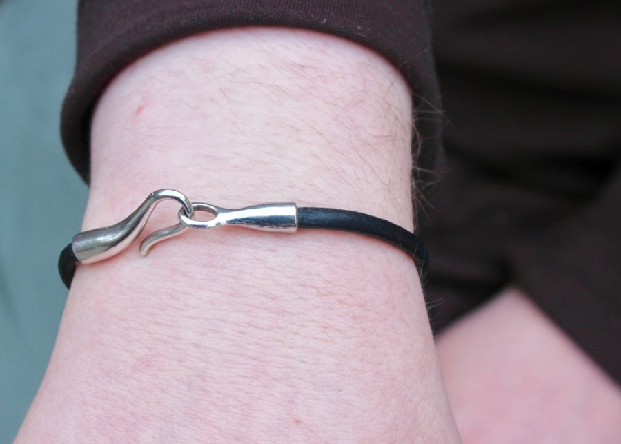 A Black leather hook bracelet on a white arm, on a dark background.