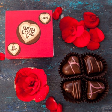 Three sweets saying things like be mine in white icing in a row on a red background, a picked apart Rose on a black background, a full Rose on a black background, and four heart shaped chocolates in a circle on a black background.