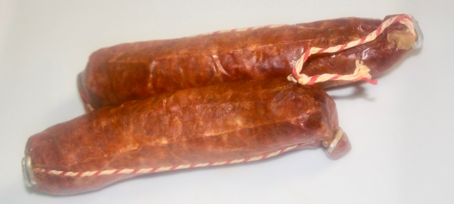 Two long red chorizo sausages with white on the edges of them, on a white background.