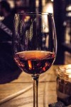 A close up shot of some dark pink Rosé Wine in a tall clear wine glass on a wooden table, on a dark background.