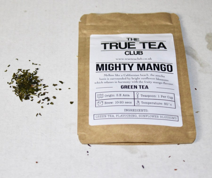 A rectangular brown pouch with a white label that has True Tea Club and Mighty Mango Green Tea written in black writing on it, with some Green Tea leaves and some Mango at the side of the pouch, on a white background.