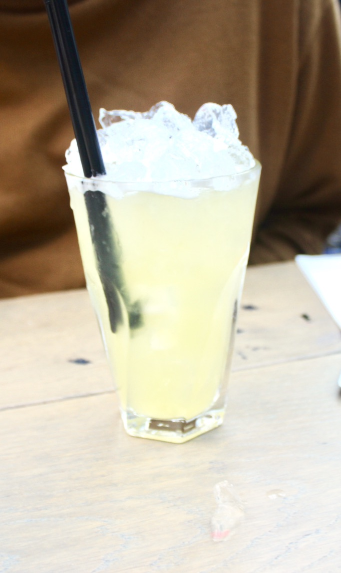 A tall glass full of pale yellow and green liquid with some clear shards of ice and two black straws on a tan table, on a dark background.