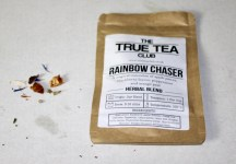 A rectangular brown pouch with a white label that has True Tea Club Rainbow Chaser Peppermint Tea written in black writing on it, with some multicoloured Tea leaves next to the pouch, on a white background.