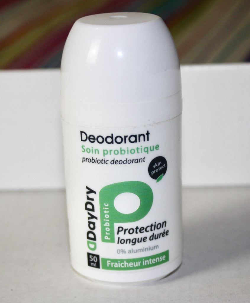 A white roll-on deodorant bottle with DayDry Deodorant and protect written in black writing, with a green letter P next to it, on a white background.