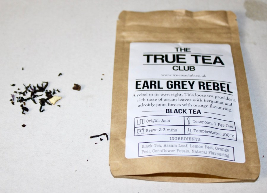 A rectangular brown pouch with a white label that has True Tea Club Earl Grey Rebel Loose Leafed Tea written in black writing on it, with some black Tea Leaves next to the pouch, on a white background.
