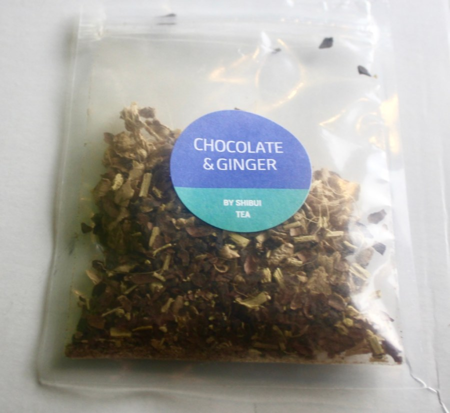 A square clear plastic bag containing some dark brown and dark orange tea leaves with a dark blue circular sticker that has Chocolate & Ginger written in medium white writing and Shibui written in smaller white writing on it, on a white background.