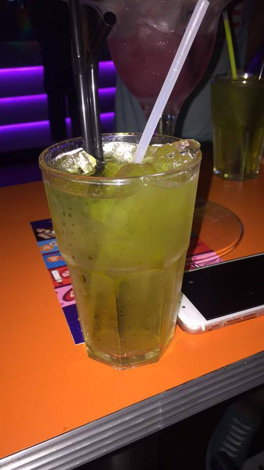 A large tumbler glass full of some light green coloured liquid, some clear ice cubes, some black straws and a glow stick, next to a white iPhone on a light wooden table, on a dark background.