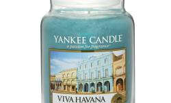 A tall glass jar full of some sea blue coloured wax with a label that has yankee candle written in white writing, Viva Havana written in black writing and a picture of a bright beach on it, on a white background.