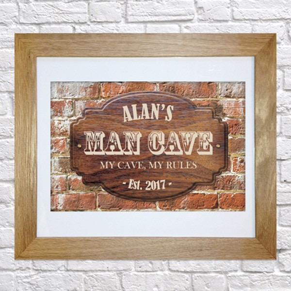 A dark grid printed picture that has Alan's Man Cave written in barber inspired writing and my man cave my rules written in smaller white writing inside a medium coloured wooden frame, on a medium coloured background.