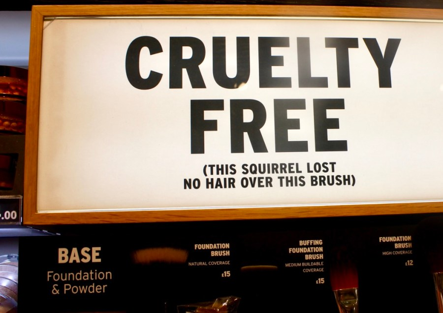 A long rectangular white board that has cruelty free written in bold black writing and this squirrel lost no hair over this brush in smaller bold writing on it, on a bright background.